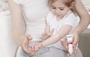 Little girl, sitting on mother´s lap, is applying Eucerin AtopiControl Acute Care cream on the crook of her arm.