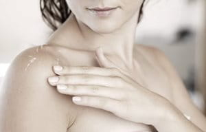 Woman with wet skin touching ger shoulder