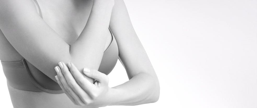 Woman wearing a bra touching her elbow