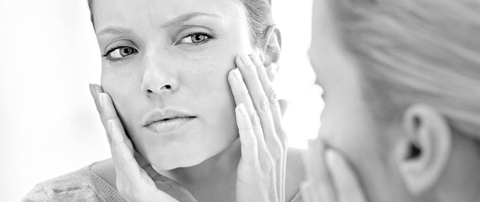Woman applying Eucerin Even Brighter Spot Corrector while watching herself in the mirror